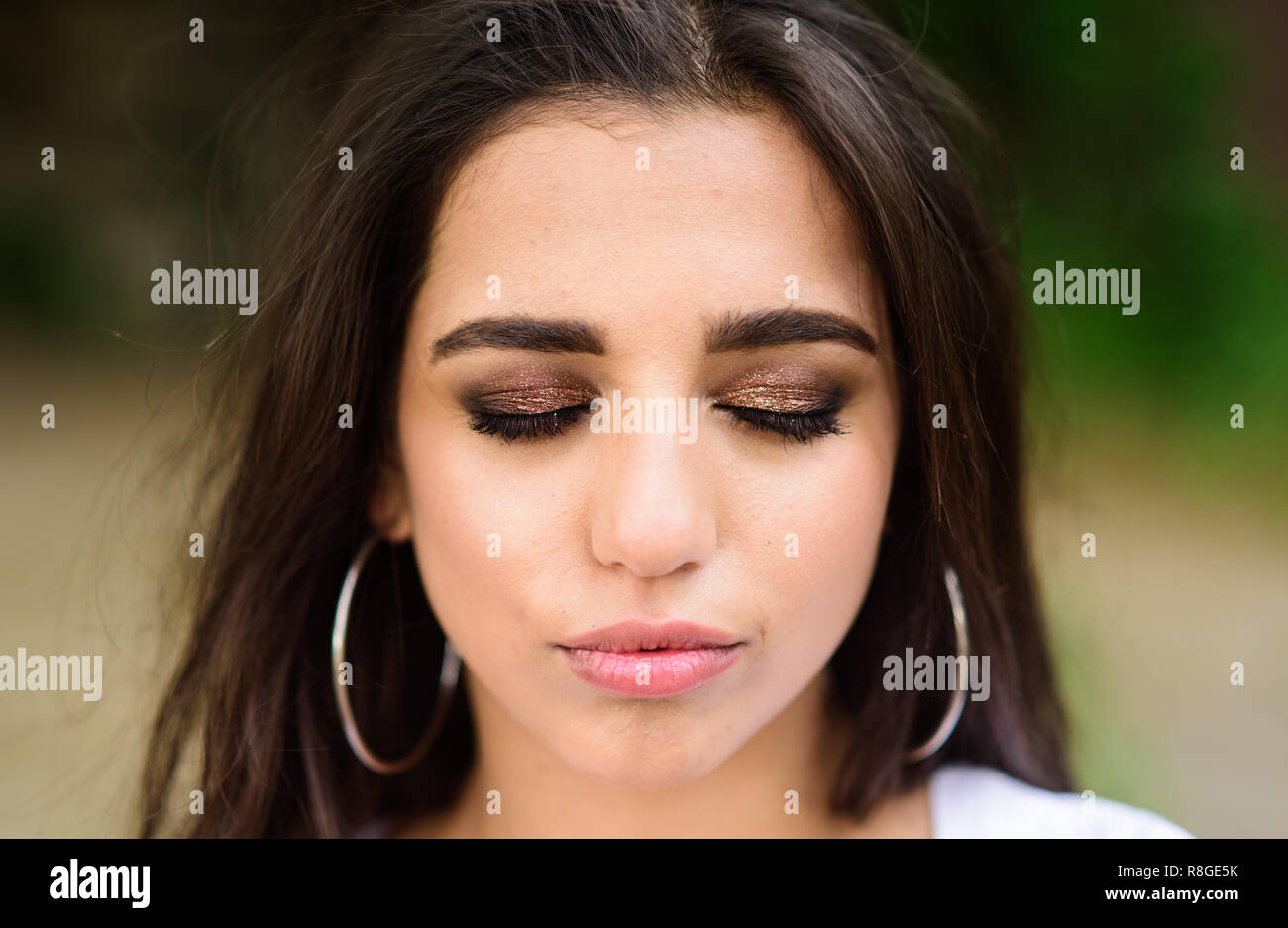 Lady relaxed face make up close eyes with shimmering eyeshadows. Make up concept. Girl wear metallic earrings. Girl attractive gorgeous brunette middle eastern appearance with make up close up. - Stock Image