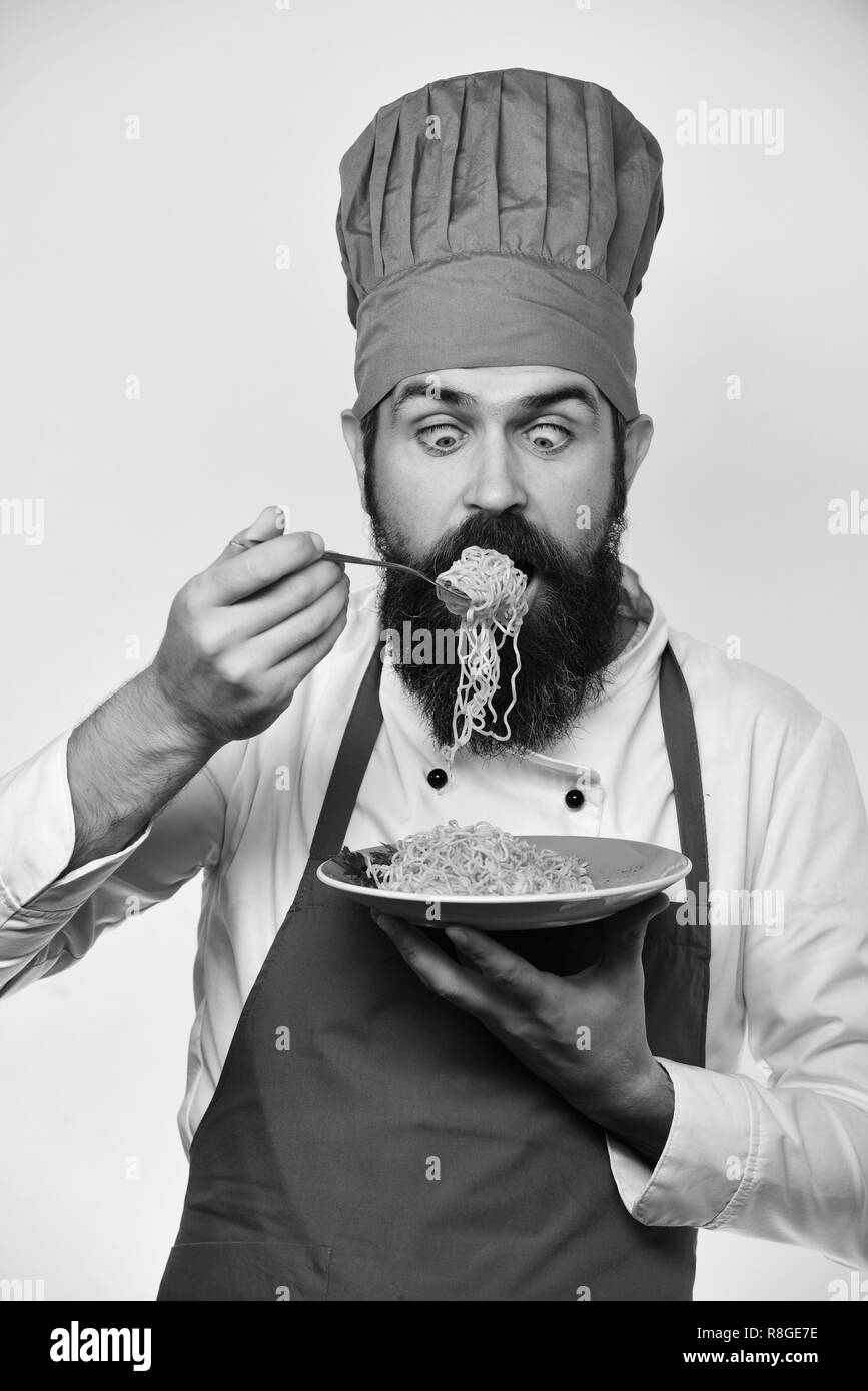 Chef eats italian or asian noodles. Man with beard holds tasty dish on white background. Traditional menu concept. Cook with shocked face in burgundy uniform looks at fork and plate. - Stock Image