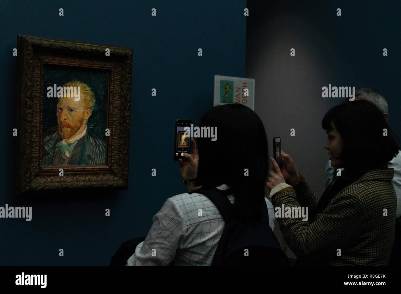 Visitors in front of Vincent Van Gogh's 'Portrait de l'artiste' (Portrait of the artist), one of the famous Dutch painter's autoportraits displayed in - Stock Image