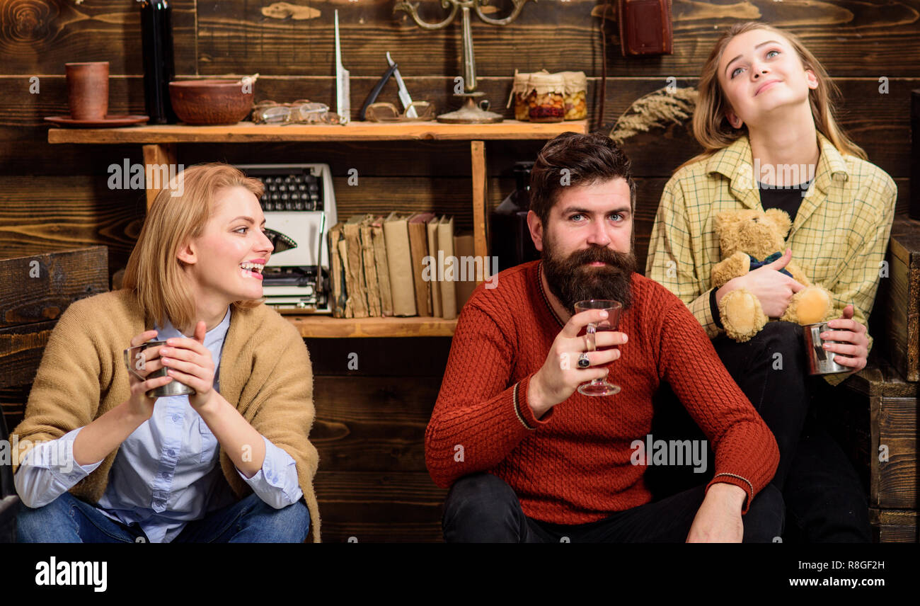 Friends have fun, speaking and drinking hot drinks in wooden interior. Friends spend leisure in cozy interior. Communication concept. Man and ladies on happy faces discussing and drinking mulled wine. - Stock Image