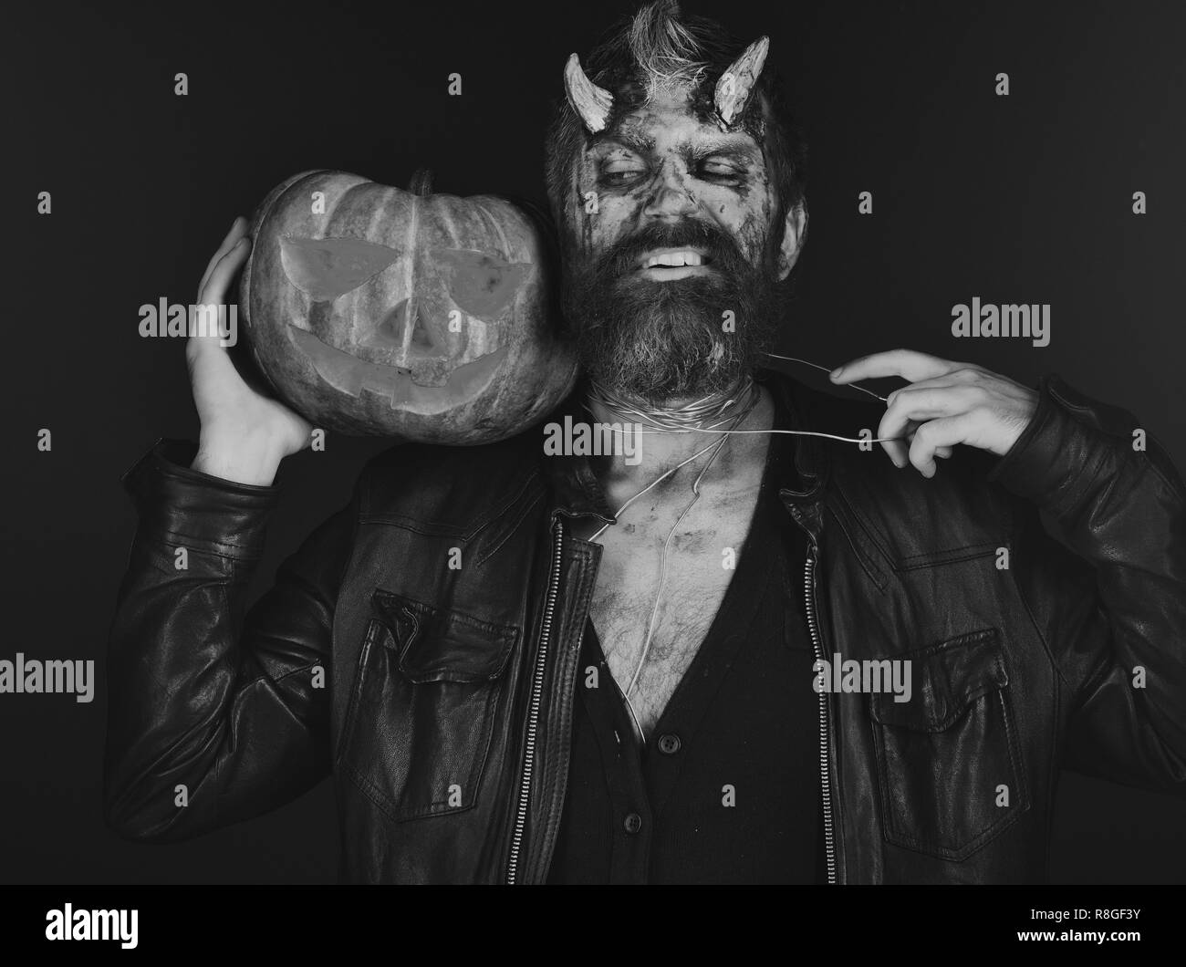 Demon with horns and tricky face holds carved jack o lantern. Man wearing scary makeup holds pumpkin on bloody red background. Halloween party concept. Devil or monster with October decorations - Stock Image