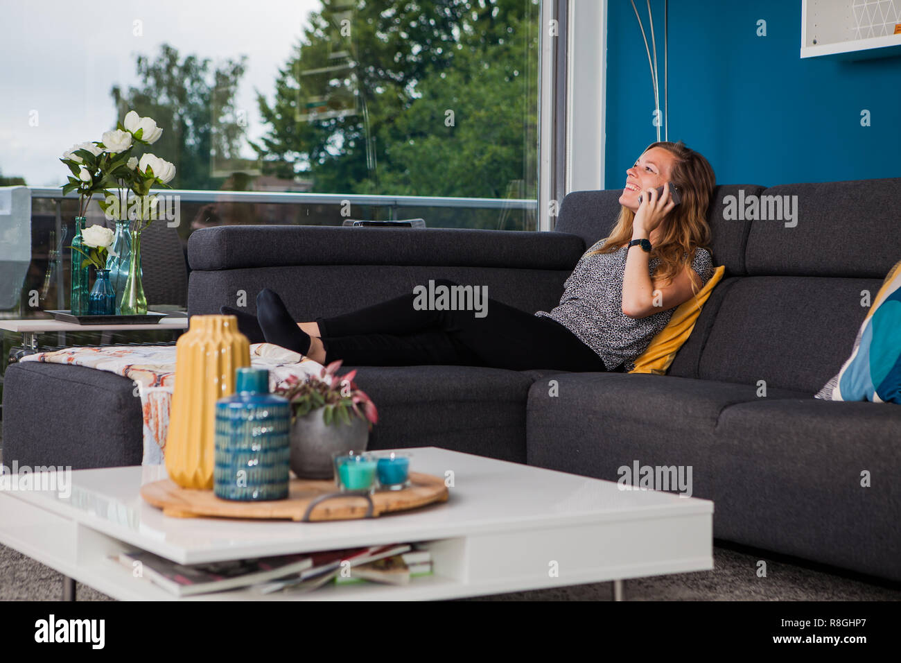 Young woman calling and laughing loudly on the couch in the living room. - Stock Image
