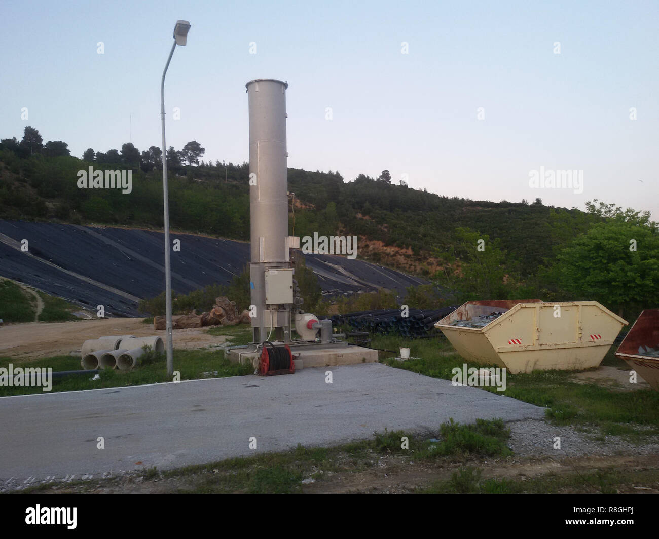 View of a sanitary landfill including a biogas flare, hdpe pipes, a skip container and the cell covered with Geo-textile membrane - Stock Image