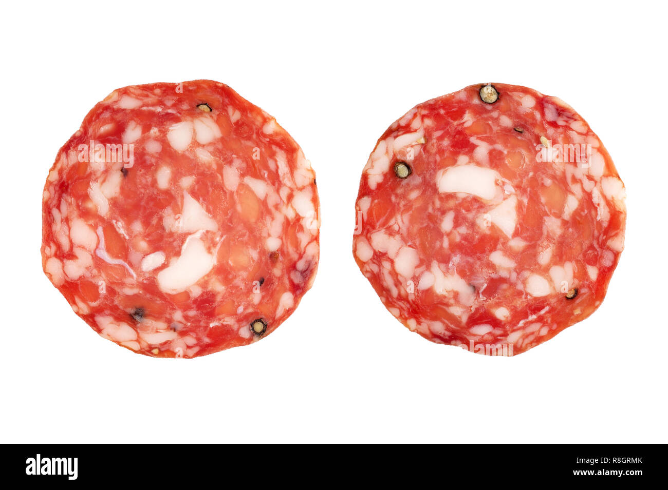 Spicy, dry, thin  sausage slices  isolated. Top view,  horizontal  orientation. - Stock Image
