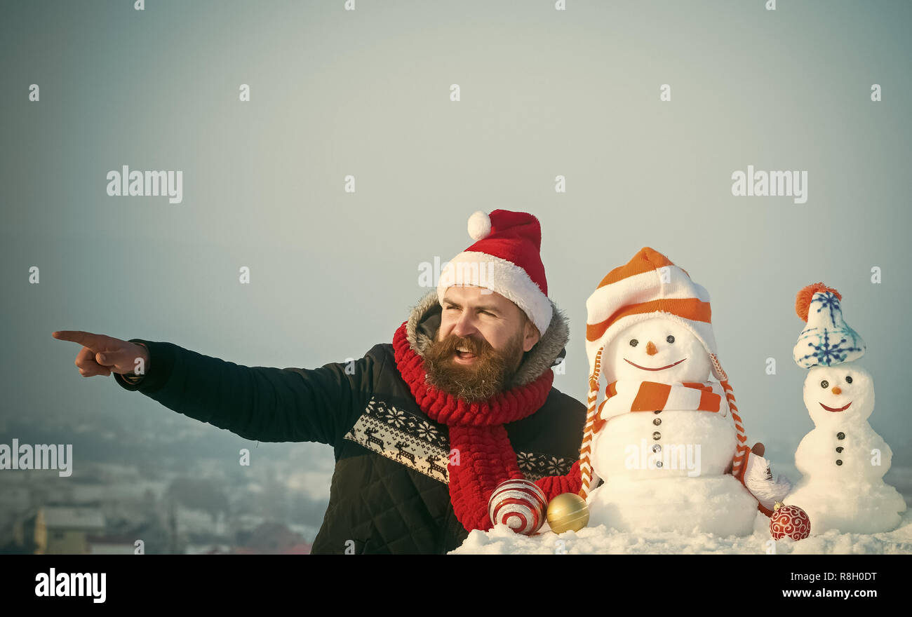 Santa man pointing finger with snowy sculptures - Stock Image