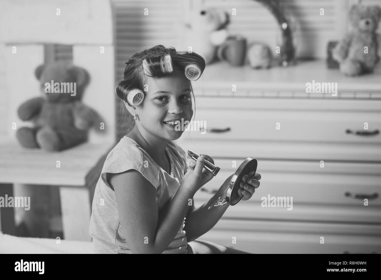 Child with moms makeup accessories and cheerful face - Stock Image