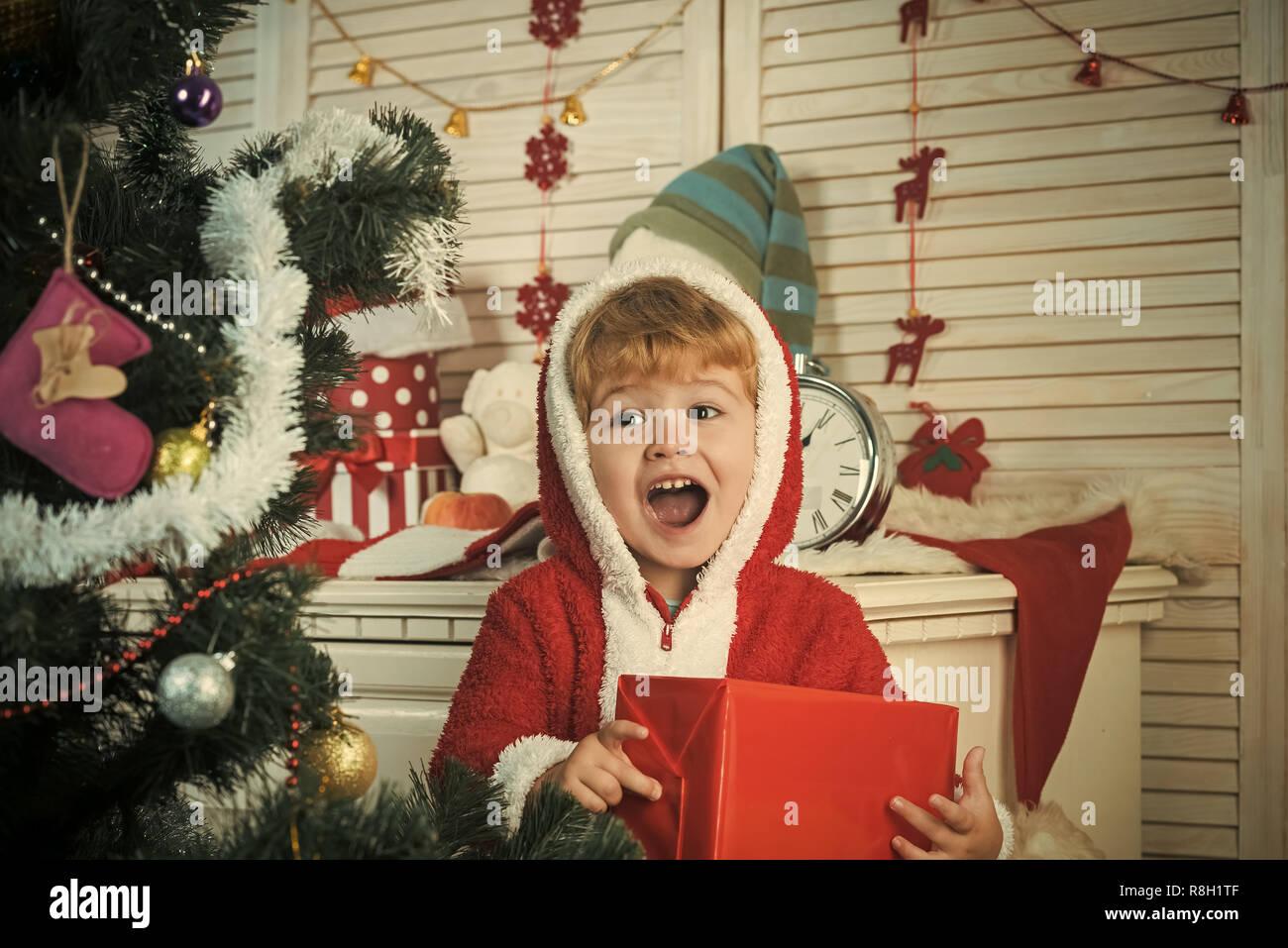 Santa claus kid decorating Christmas tree.. - Stock Image