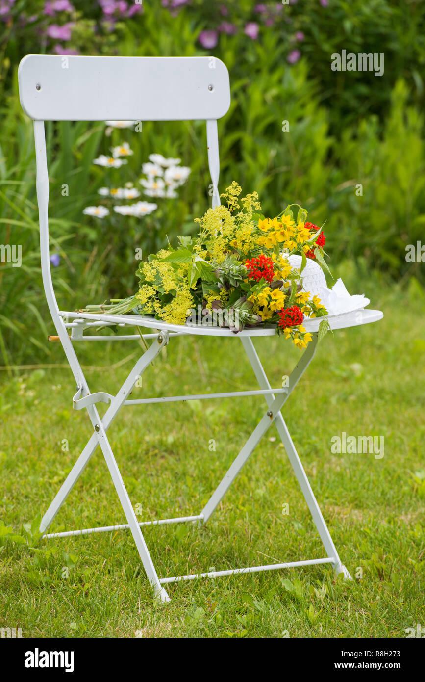Gartenstuhl mit bunten Sommerblumen - Stock Image