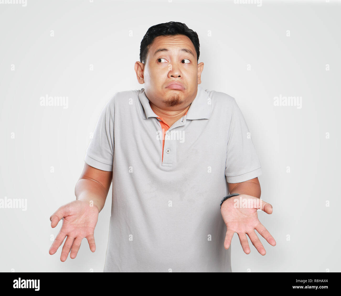Photo image portrait of a cute young Asian man showing I don't know gesture, shoulder shrug and looking to the side - Stock Image