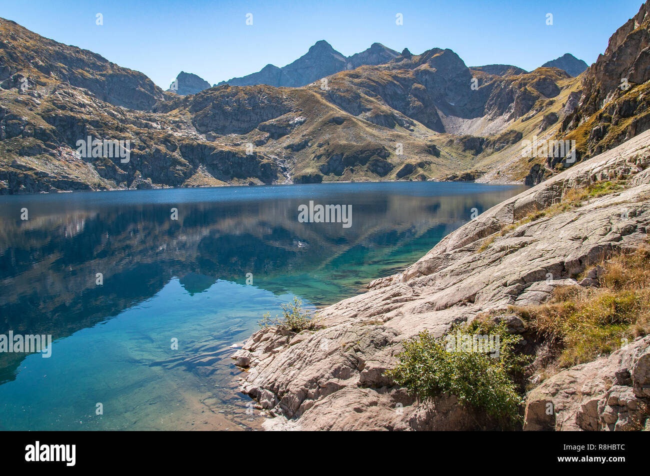 The shores of Lac d'Artouste in the Fench Pyrenees on a calm Autumn day with the mountains reflecting in the water Stock Photo