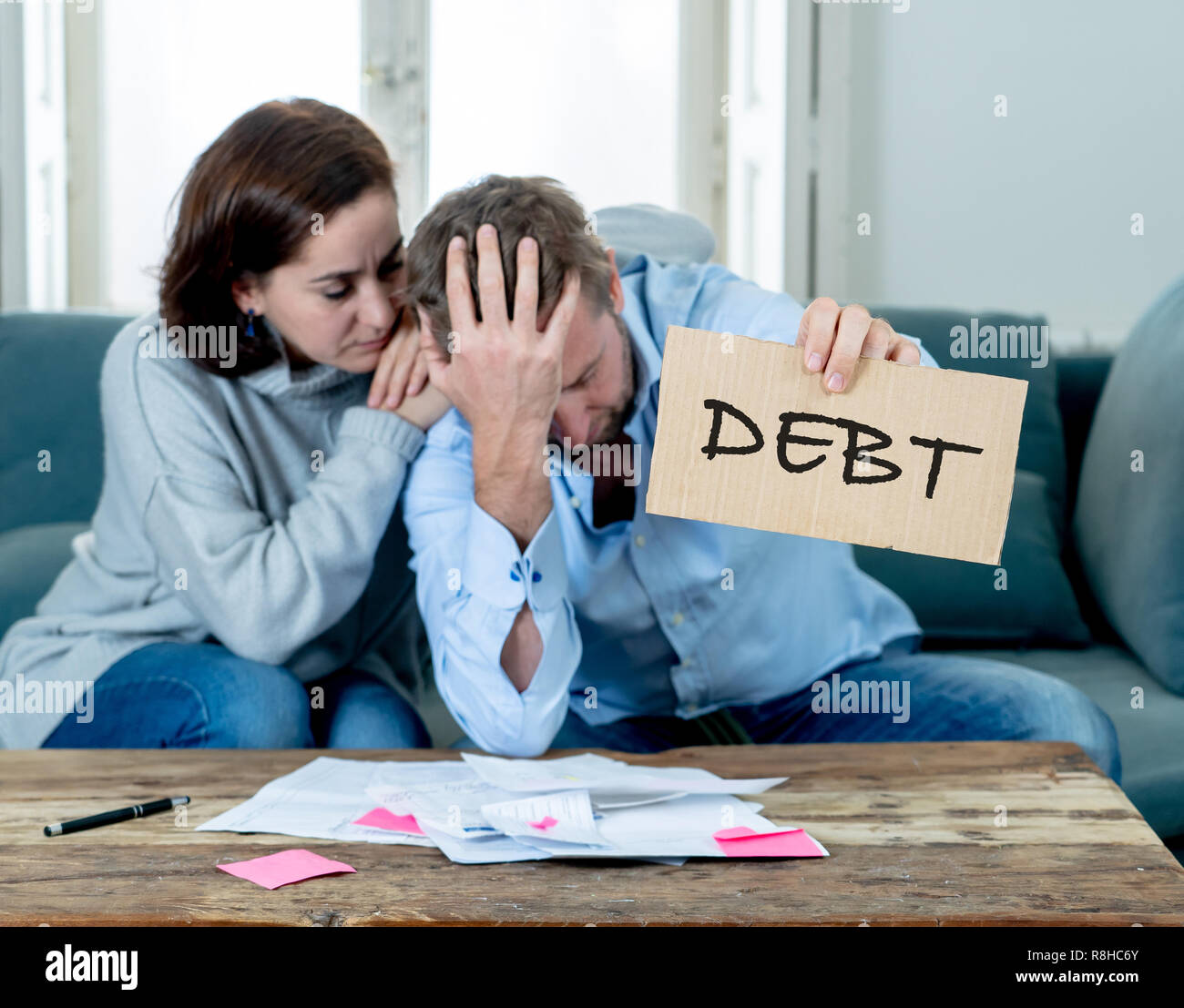 Stressed and depressed young couple having many debts in accounting home finance paying bills mortgage bank statements and expenses feeling desperate  - Stock Image