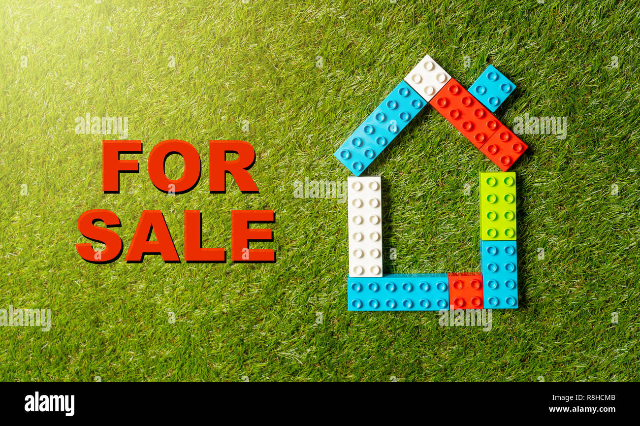 Conceptual picture of children toy blocks house and tex For Sale written on green grass field top view for Property investment Real estate Saving and  - Stock Image