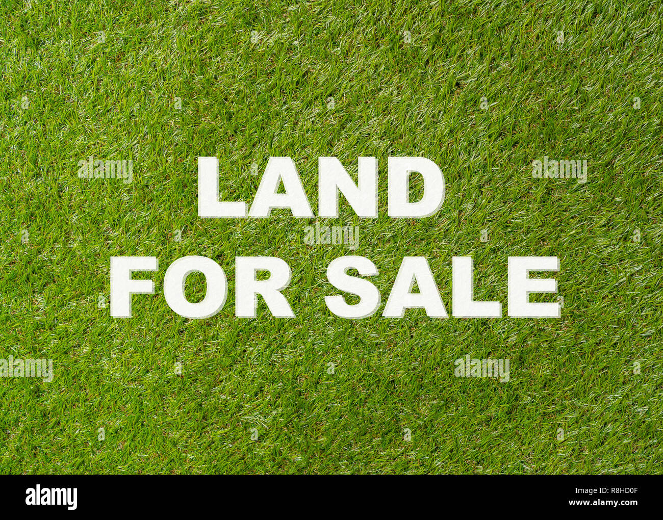 Conceptual image with text written Land for Sale on green grass field background of Property investment and market and Real estate agency and industri - Stock Image