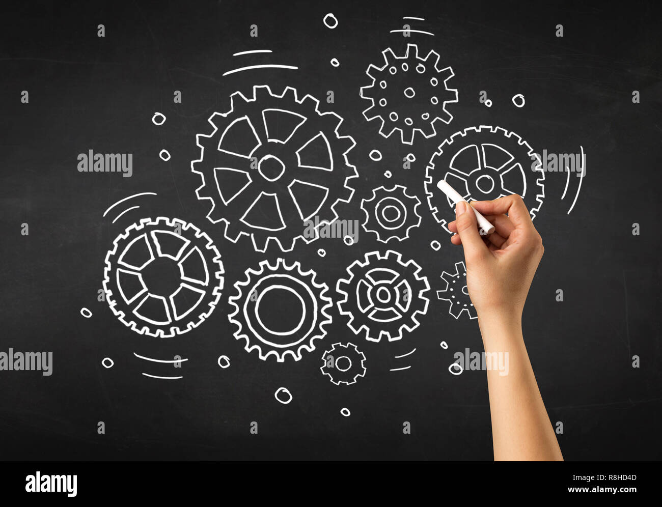 Female hand holding white chalk in front of a blackboard with gears drawn on it - Stock Image