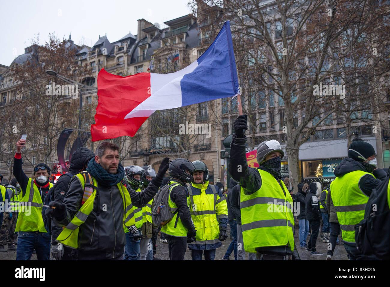 Champs-Elysees, Paris, France. 15th Dec 2018. Protesters waving french flag. Yellow Vests (Gilets Jaunes) protests, Champs-Elysees, Paris, France, DEcember 15, 2018. Credit: Julien Garnier/Alamy Live News - Stock Image