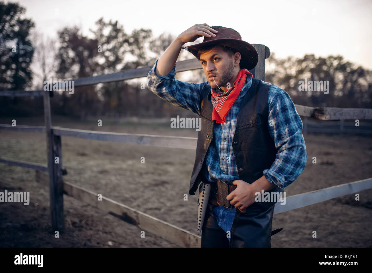 Young cowboy in leather jacket and hat poses against horse corral ... bc176a866398