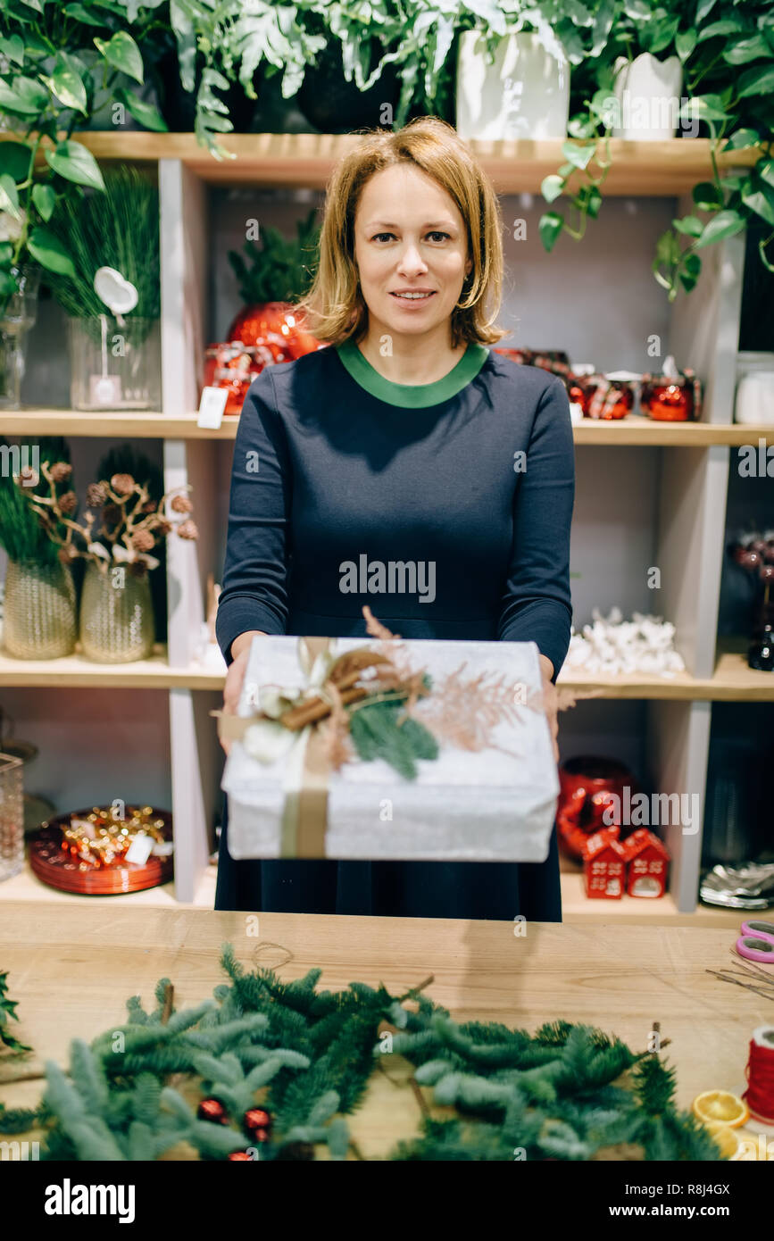 Female seller shows christmas gift box with handmade wrapping. Woman wraps present on the table, festive decor