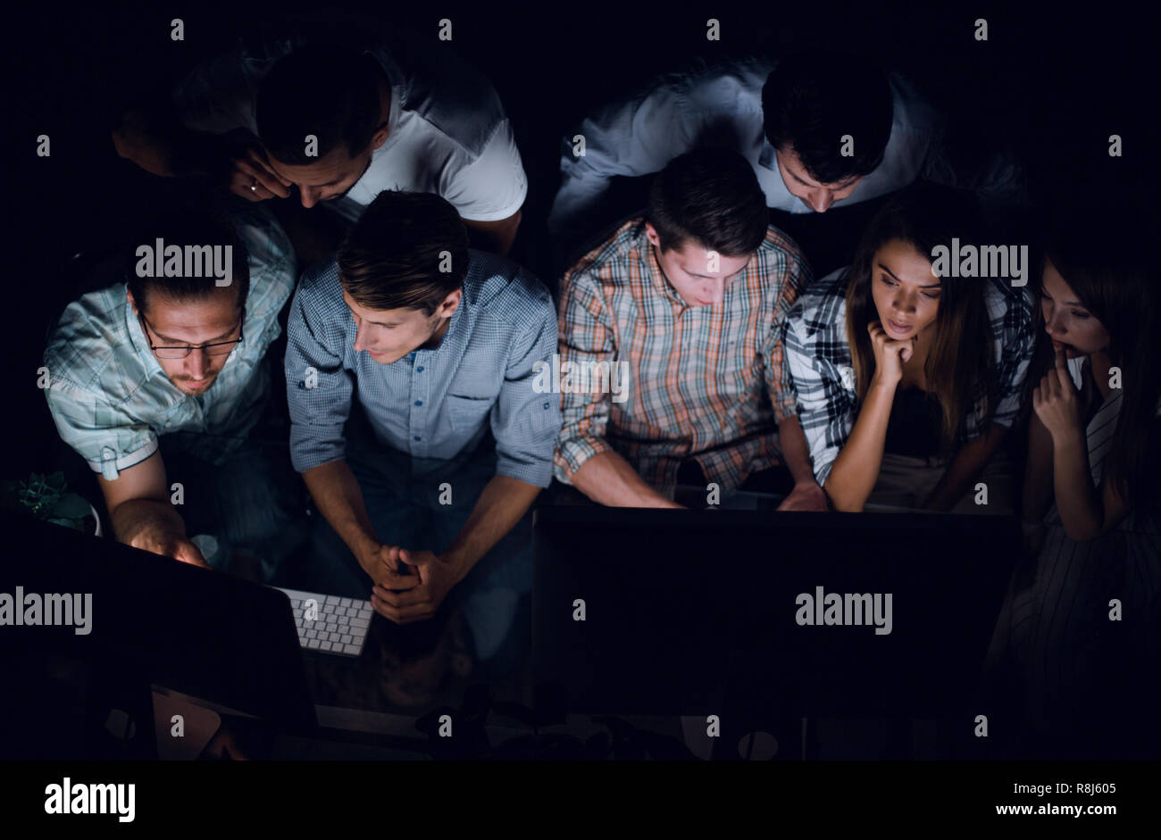 business team closely monitors the information on their computers - Stock Image
