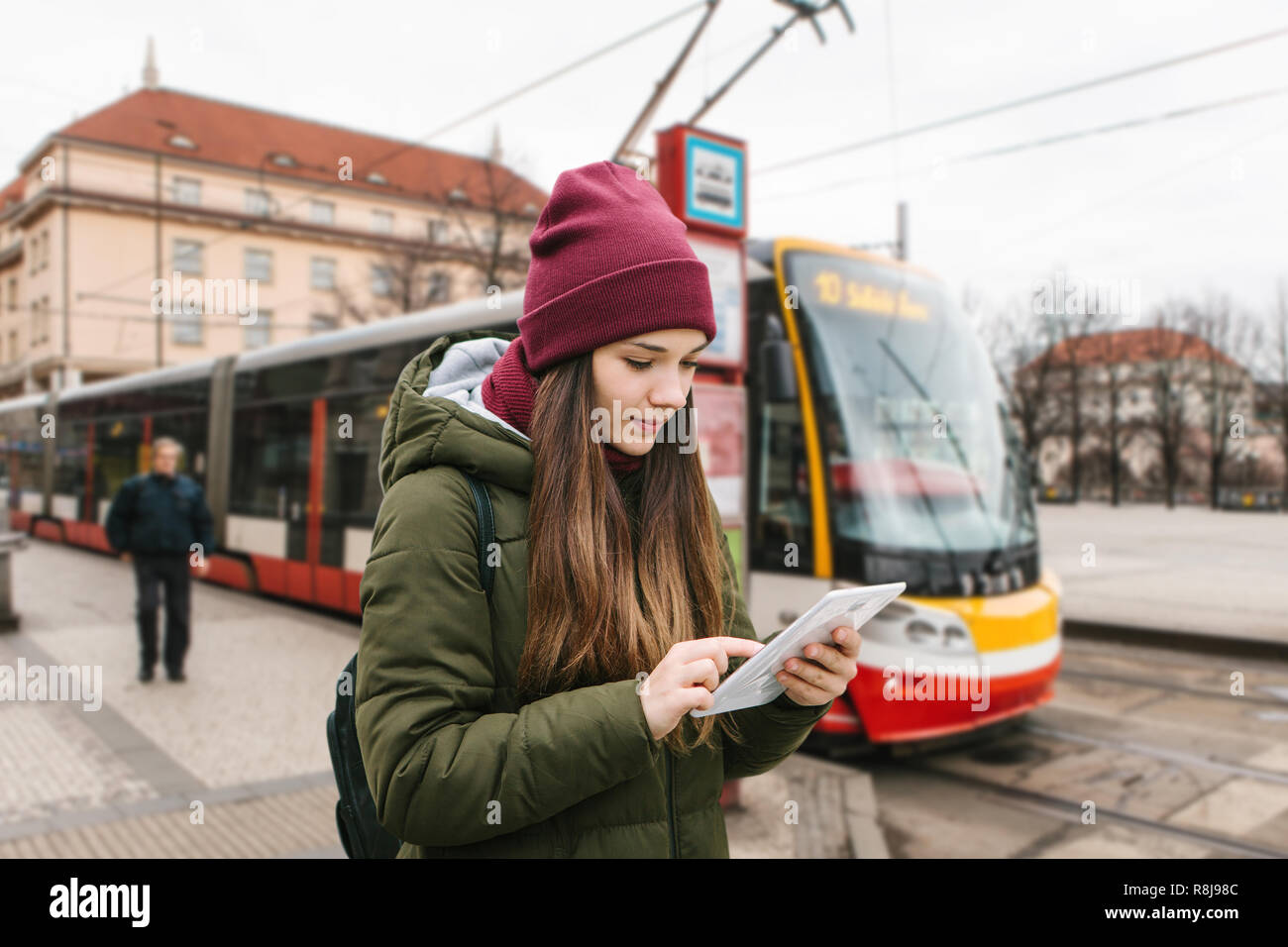 A girl or a tourist got off the tram stop from a tram and looks at a tablet city map or a mobile application. She uses the internet or she is online. In the background unrecognizable person and tram - Stock Image