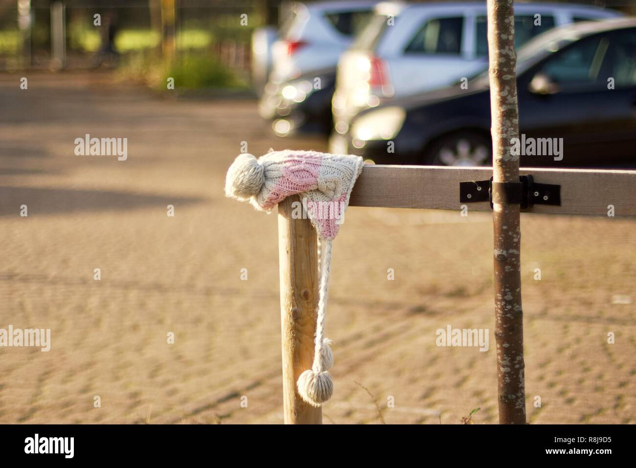 A pink and white woollen children's hat abandoned or lost in a car park - Stock Image