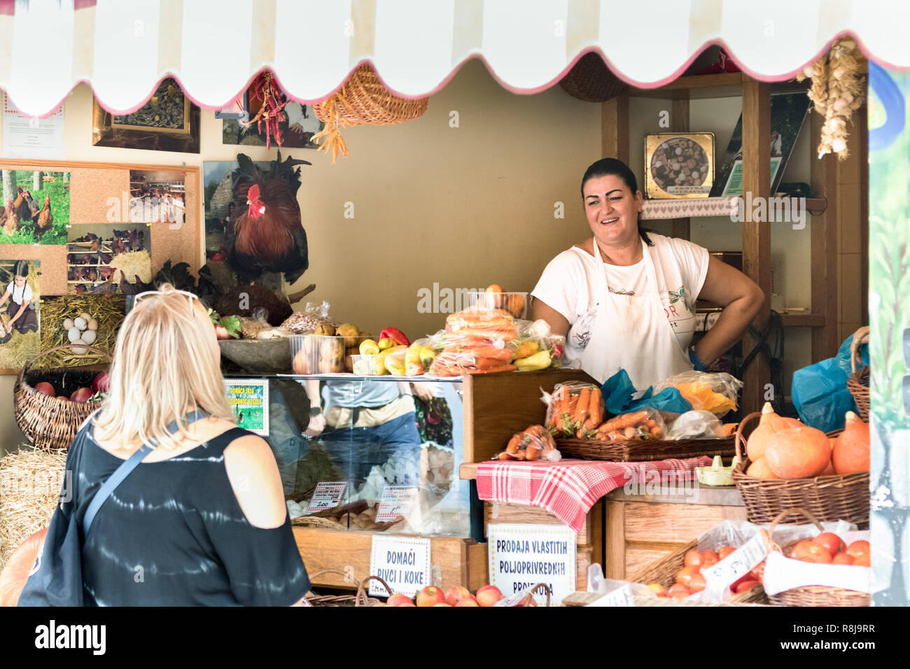 Croatia, Split - September 22th, 2018: A female seller speaking with happiness with a customer at her grocery store in a public market in Split, Croat - Stock Image