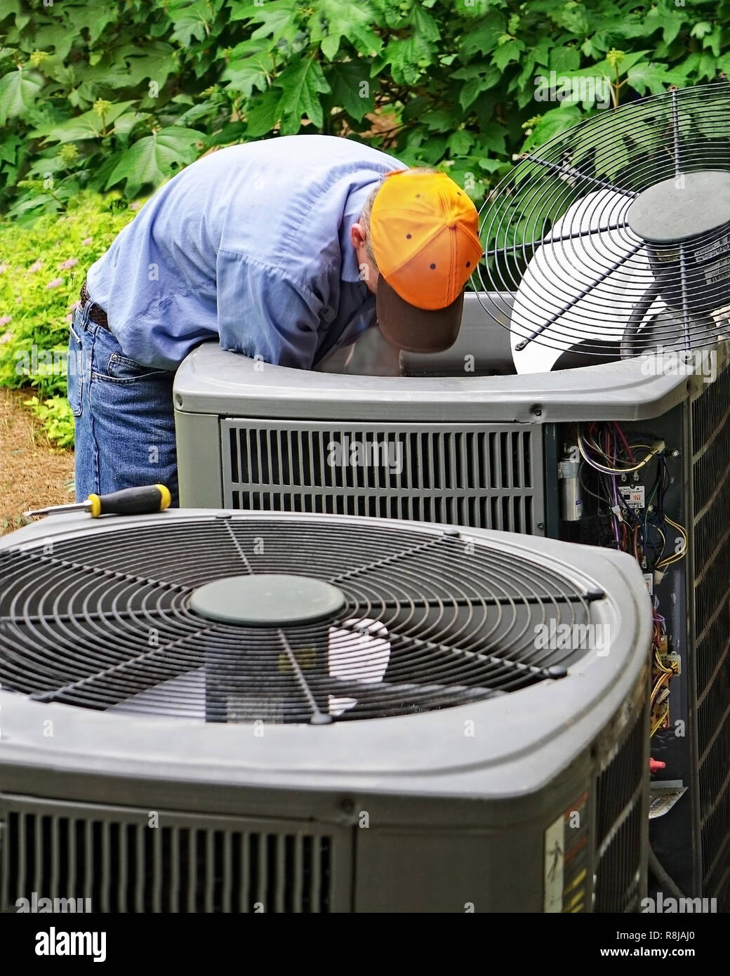 Repairman working on an air conditioner unit at the back of a house Stock Photo