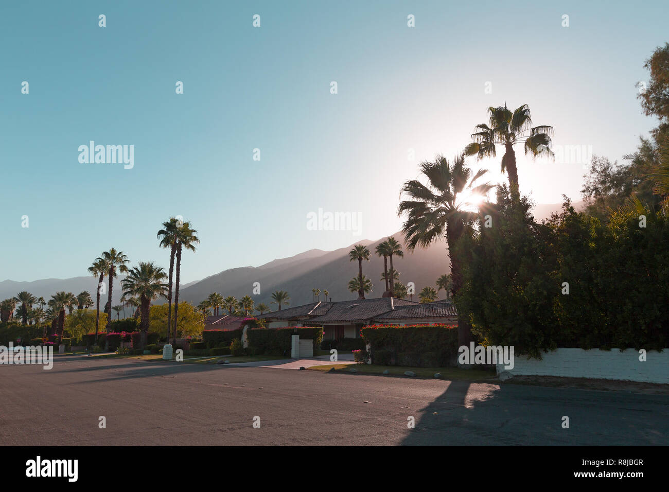 The sun goes behind the mountains before the dusk in Palm Springs, California, USA. A stream of sunlight on the mountains surrounding Palm Springs tow Stock Photo