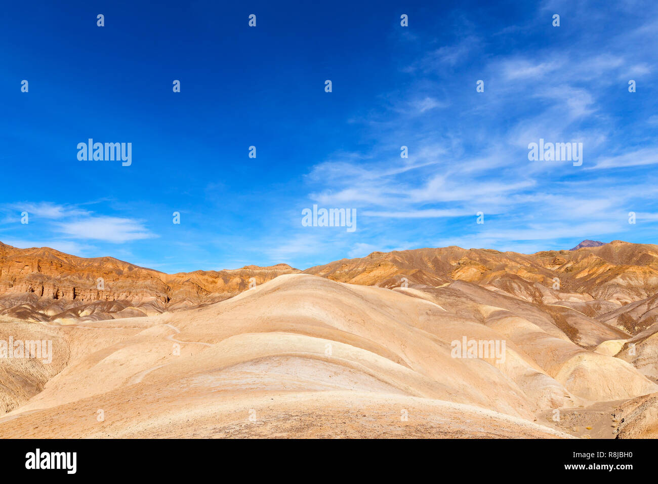 Death Valley National Park panorama near Zabriskie Point. Mountainous landscape of badlands in the morning under blue skies. - Stock Image