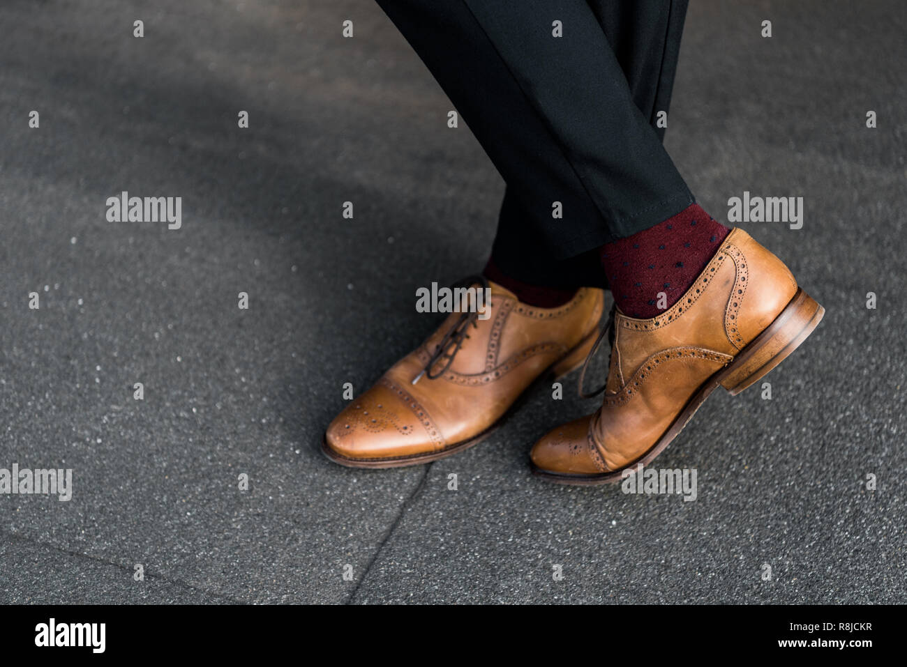 cropped view of male crossed legs in burgundy socks and oxford shoes - Stock Image