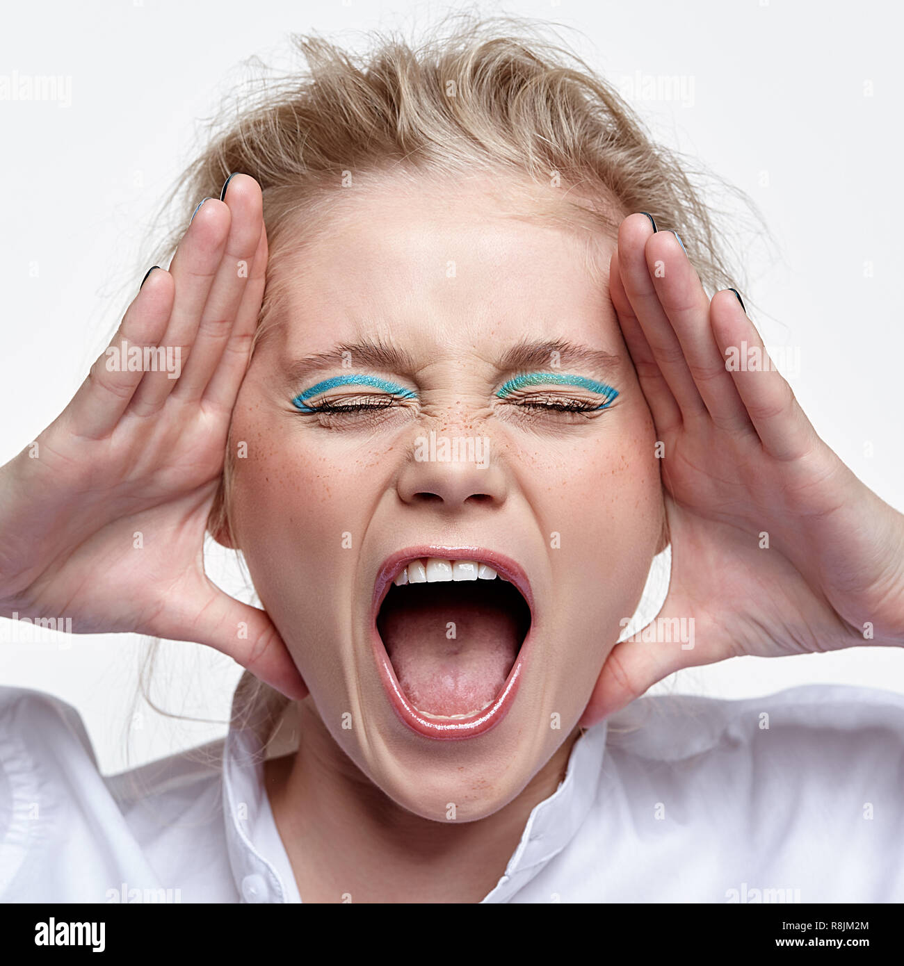 Emotional portrait of a young blonde woman on gray background. Female put palms to face and scream loudly - Stock Image