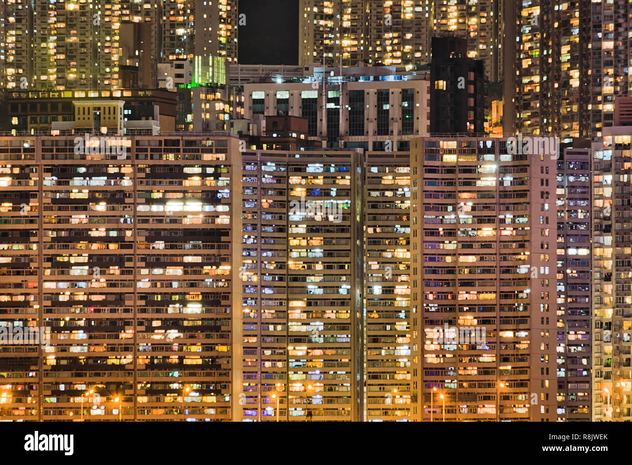 Densely populated skyscraper living towers of houses in Hong Kong at night with bright illumination of windows on island's waterfront. Stock Photo