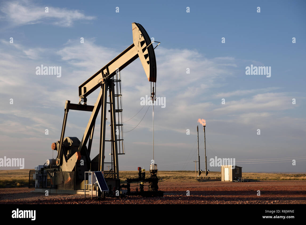 Natural gas flare and crude oil pump jack, Niobrara shale oil and gas production in Wyoming, with copy space. - Stock Image