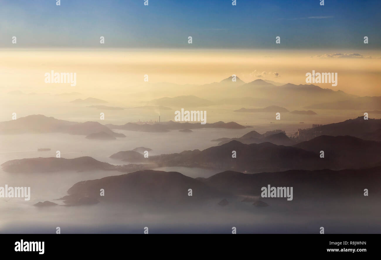 Elevated aerial view over achipelago of islands around Hong kong and Lantau covered by clouds and mist during sunset hour. - Stock Image