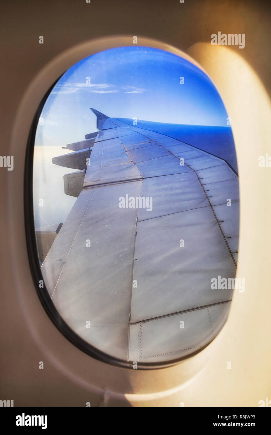 Oval of open viewing passenger window with surface of airplane wing and engines high in stratosphere during long distance flight in blue sky. - Stock Image