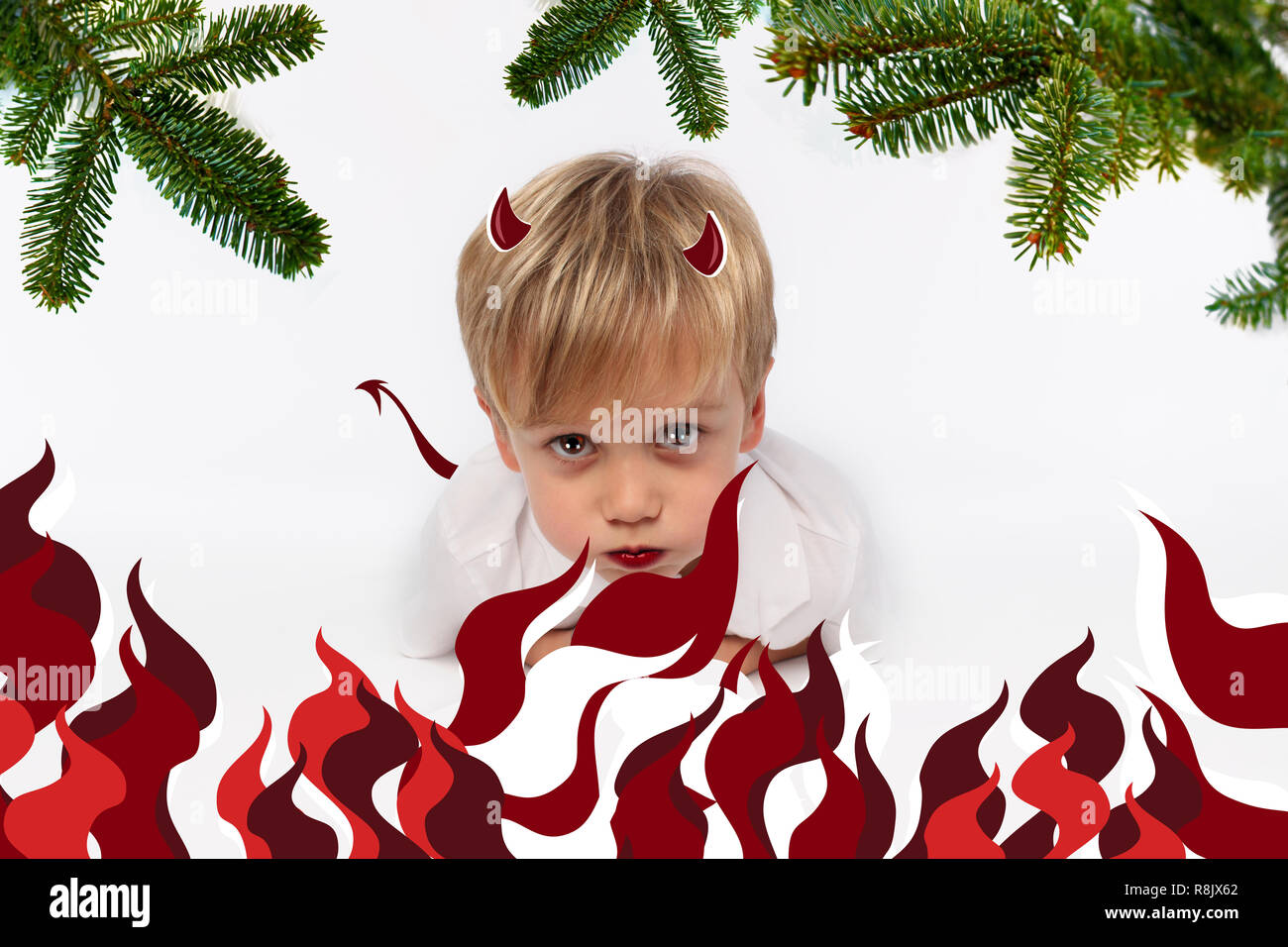 Naughty or good child for Christmas card? PF or letter to Santa-Claus for Christmas. Little child boy appearing as an adorable angelic devil Stock Photo