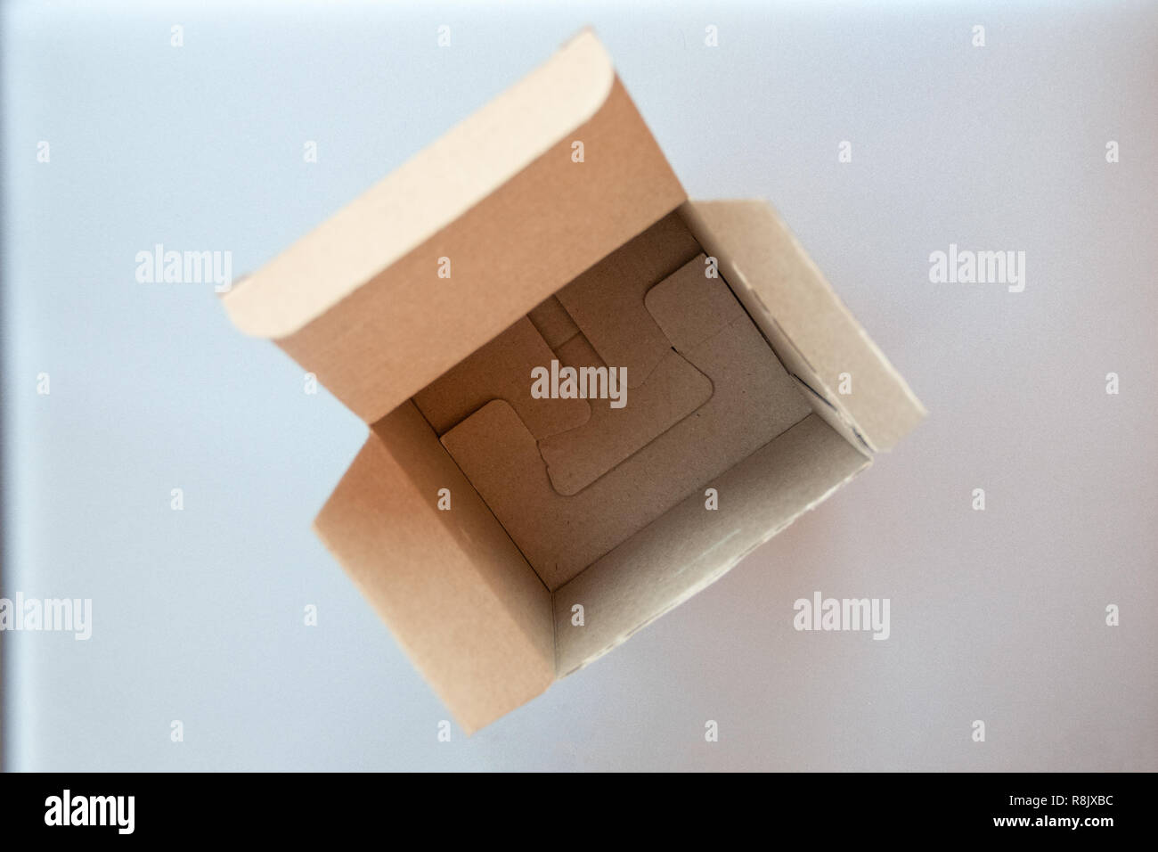 Opened big square cardboard craft gift box on the silver gray metal background - Stock Image