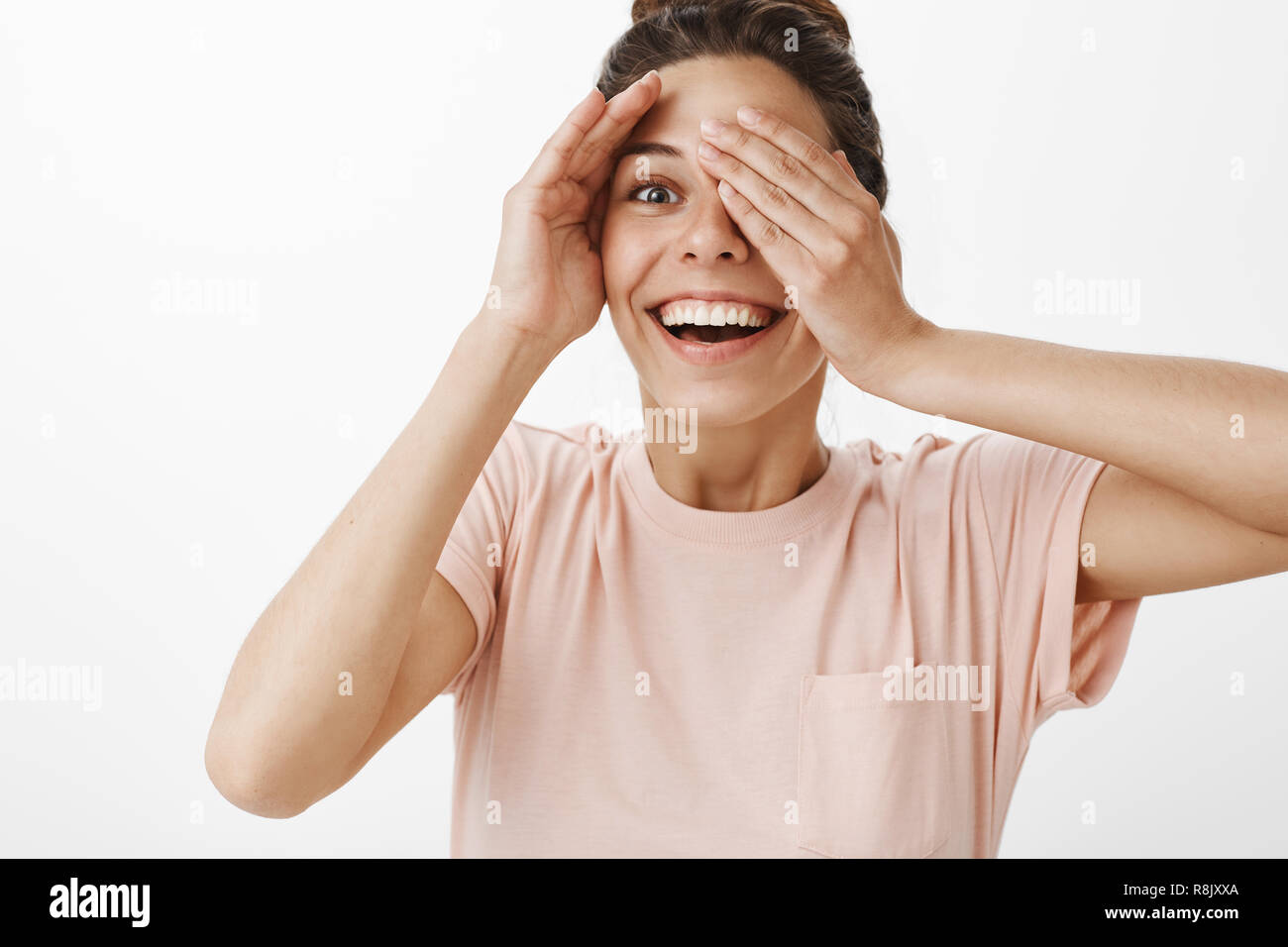 Studio shot of excited girl cheating and peeking through fingers as waiting for surprise being asked to close eyes smiling broadly with amused and joyful expression reacting to awesome present - Stock Image