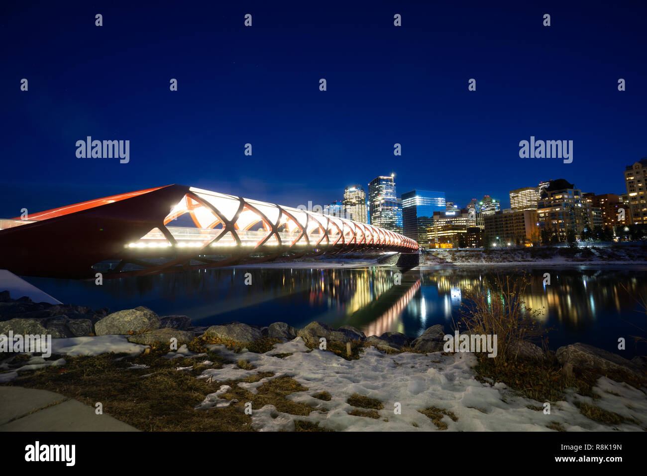 Bridge over river with Night city Skyline in background - Stock Image