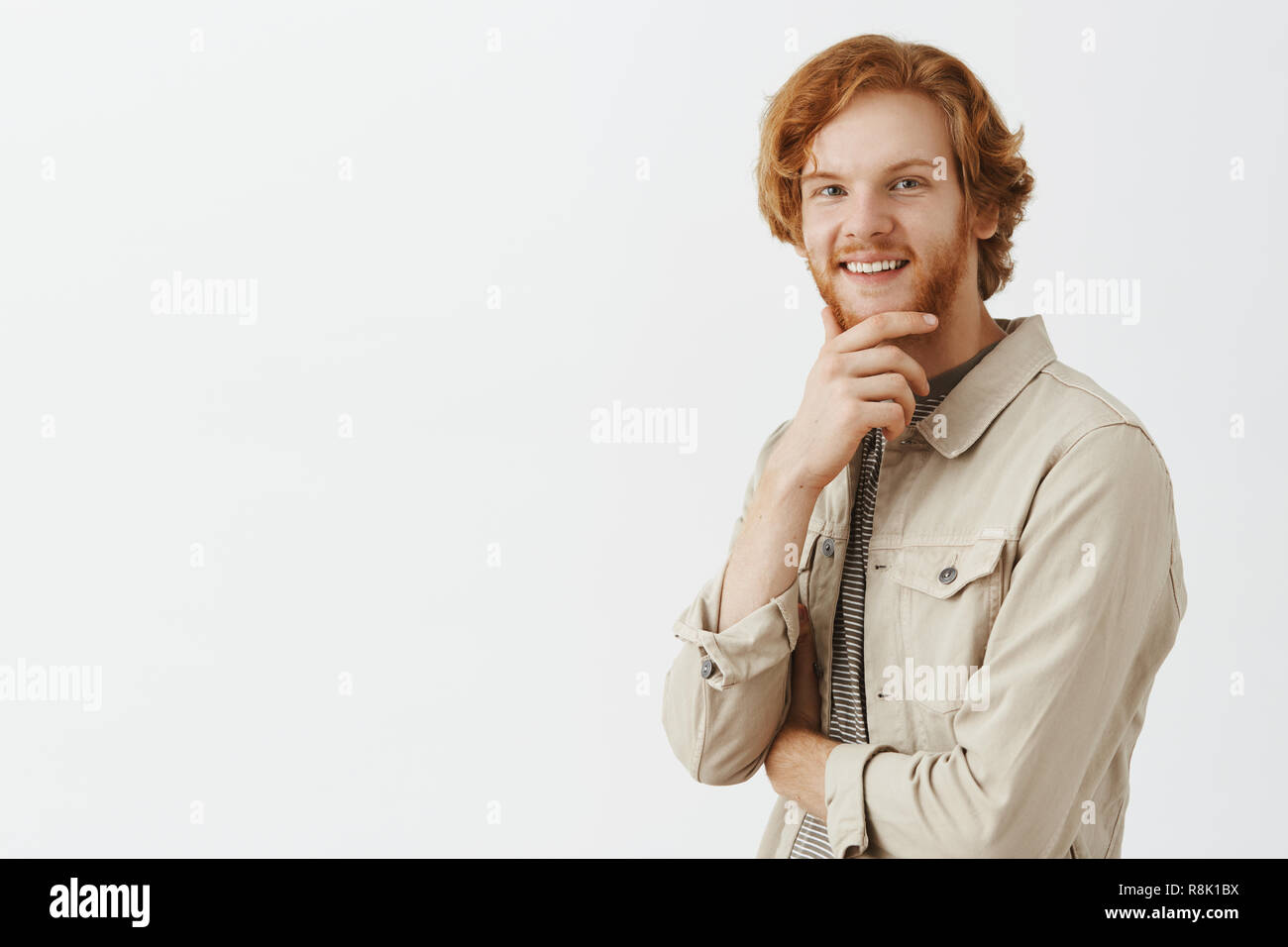 Portrait of intrigued and curious redhead happy guy receiving intersting offer consedering to except it rubbing beard and smiling broadly at camera thinking, making decision or choice - Stock Image
