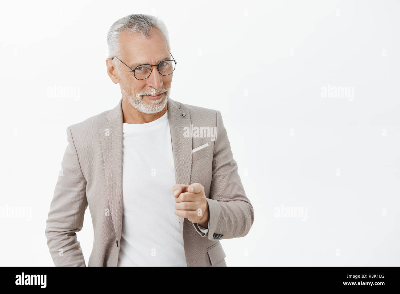 We need you man. Portrait of happy amused and tricky mature macho businessman in glasses and suit smiling looking and pointing at camera as if hinting or picking someone to join team - Stock Image
