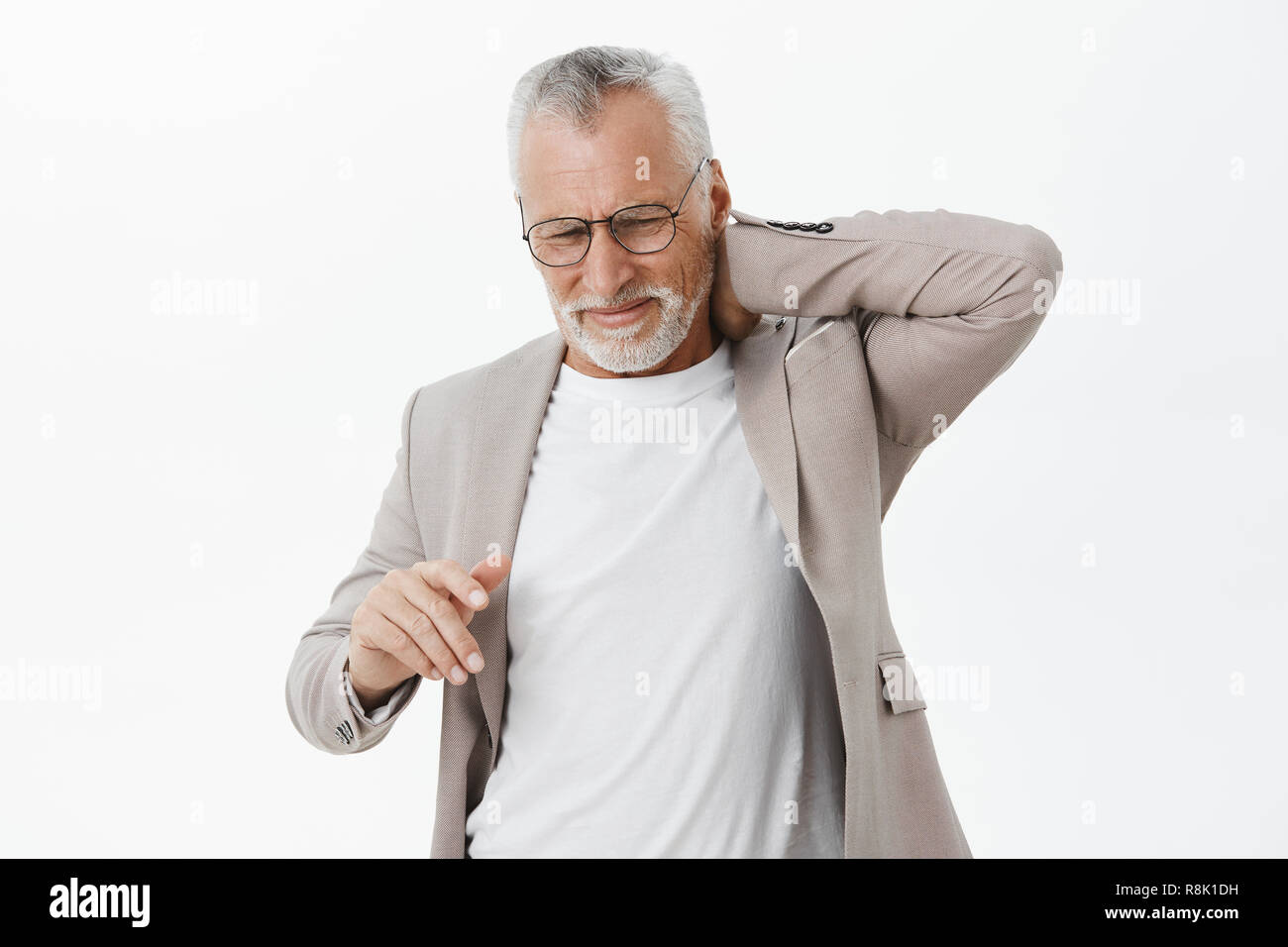 Man feeling pain in spine after hardworking sitting for long time. Portrait of displeased bothered mature male with white beard and hair in glasses touching back of neck complaining on pain - Stock Image
