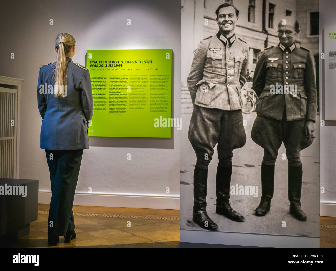 Commissioned officer of the German army standing next to the picture of von Stauffenberg and von Quirnheim, heroes of the Resistance. - Stock Image
