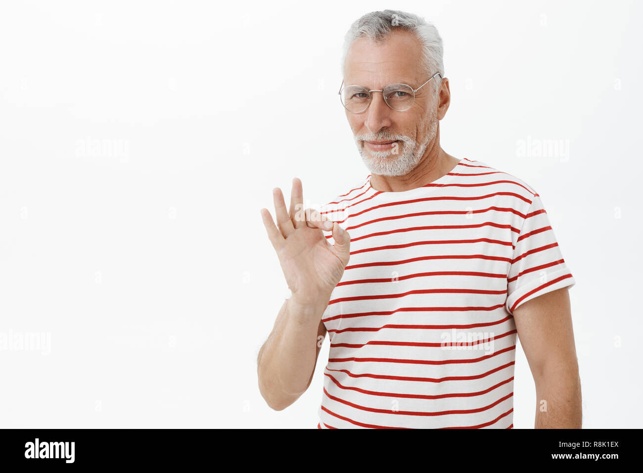 Old charismatic and self-assured man staying chill and cool showing okay gesture and smiling satisfied at camera assuring he got everything under control posing confident and assertive over grey wall - Stock Image