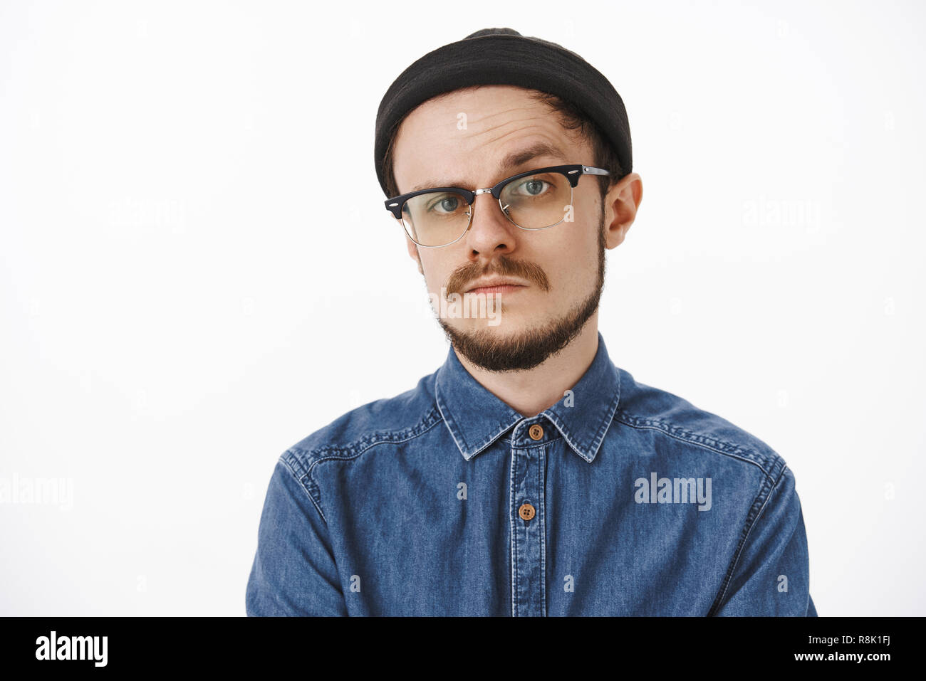 Doubtful and uncertain serious-looking bossy male entrepreneur in black beanie shirt and glasses raising one eyebrow in hesitation and disbelief standing unemotive and suspicious over gray background - Stock Image