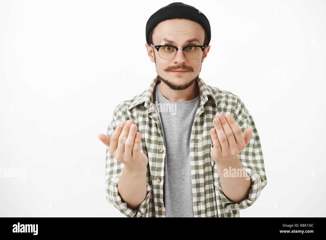 Come on closer. Serious-looking skilfful artistic bearded guy in glasses and black beanie raising palms near body asking approach to him or give something wanting hold item in hands over gray wall - Stock Image