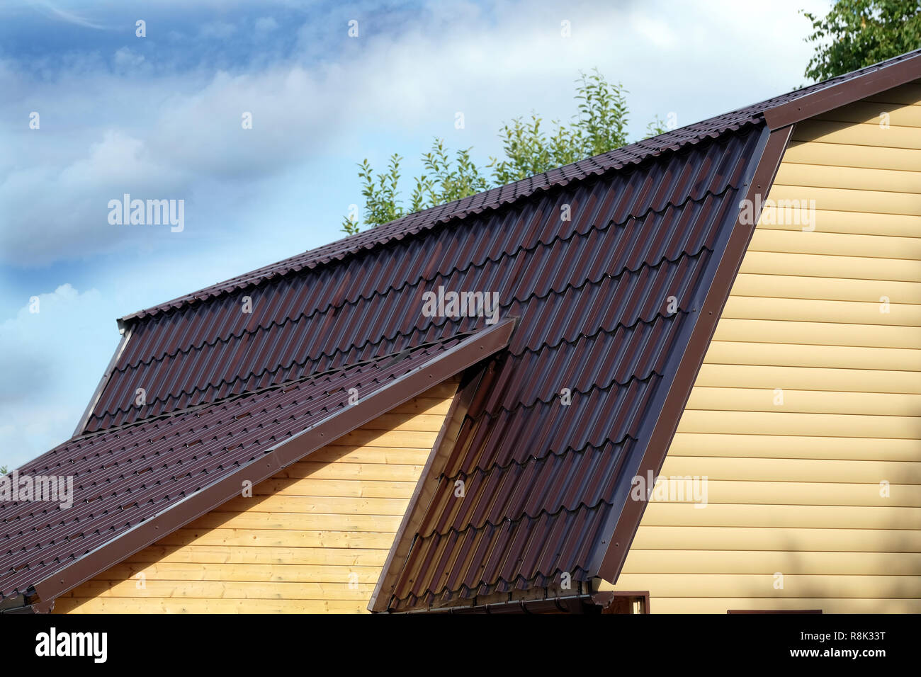Brown metal roof of rural house covered with yellow siding over blue sky with clouds on sunny day side view - Stock Image