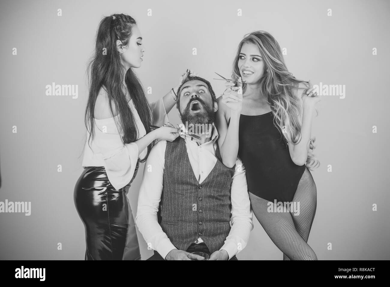 female hairdresser is cutting hair of bearded man - Stock Image