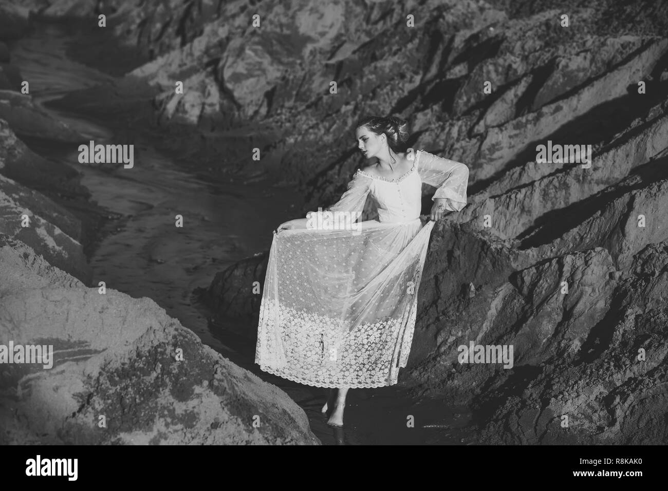 Woman in white dress pose in water, fashion - Stock Image