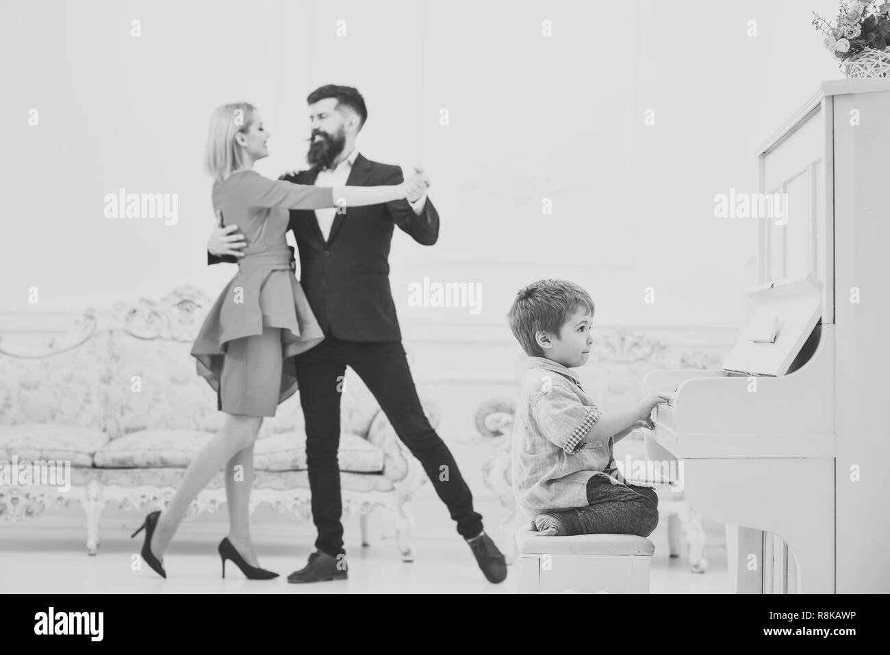 Boy adorable try to play piano musical instrument, while parents dancing. Musician education concept. Child sit next to piano, play music, white interior background. Rich parents enjoy parenthood. - Stock Image