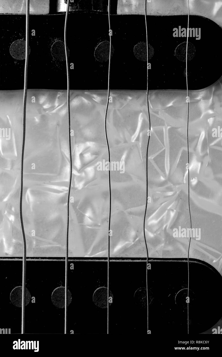 Wavy guitar strings on an electric guitar - Stock Image